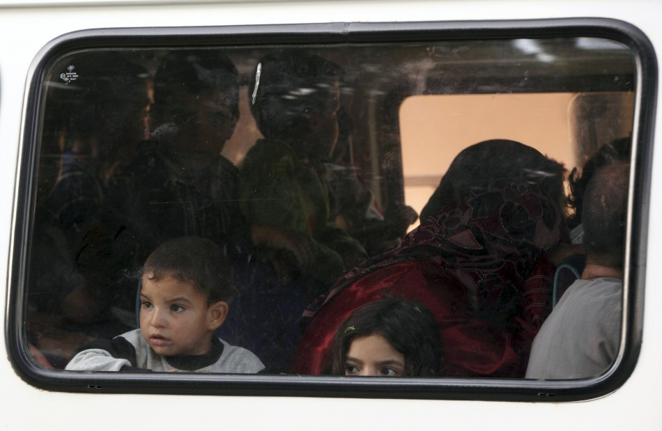 Syrian refugee children look out of a window of a bus as they are driven to a refugee camp in the Turkish border town of Yayladagi