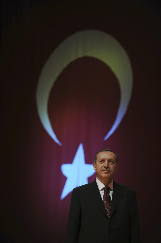 TurkisPrime Minister Recep Tayyip Erdogan standing in front of Turkey's national flag