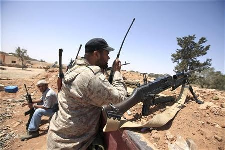 """A Libyan rebel fighter uses a walkie talkie at their position in Misrata""""s western front line,"""