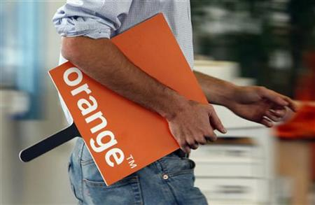 An employee holds a logo for the Orange mobile phone network provider in a retail store in Bordeaux