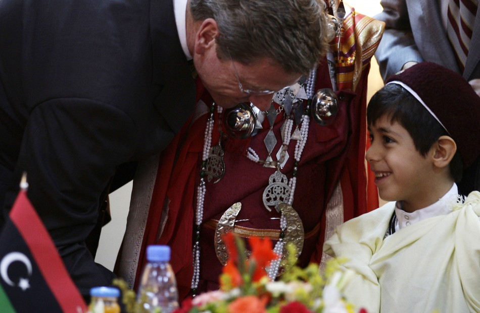 German Foreign Minister Guido Westerwelle shakes hands with a Libyan boy in traditional clothes after a news conference in Benghazi