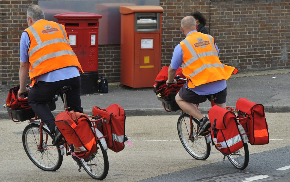 Postal workers return to a delivery office in west London