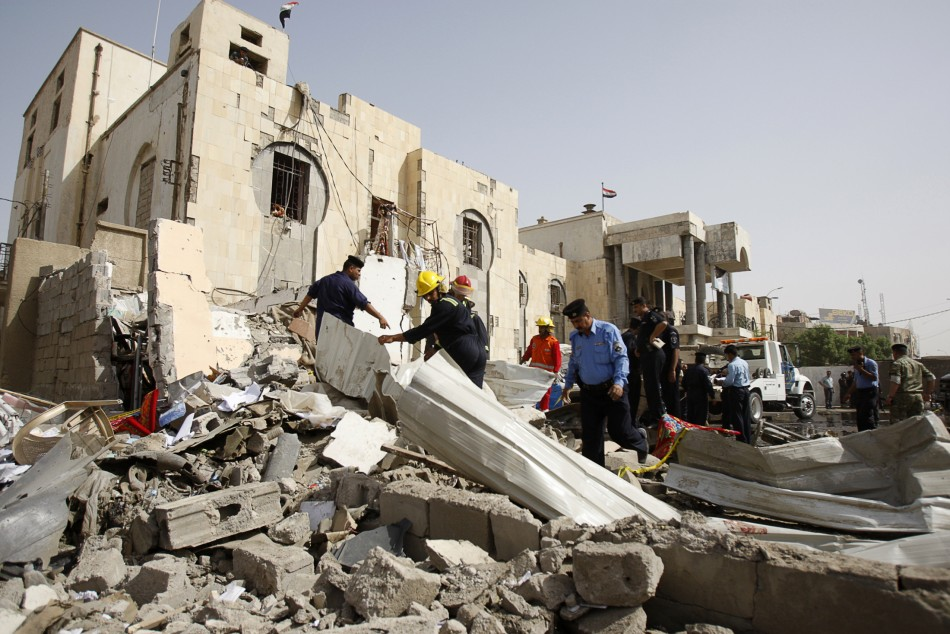 Security personnel and rescue workers gather at the site of a bomb attack in Basra