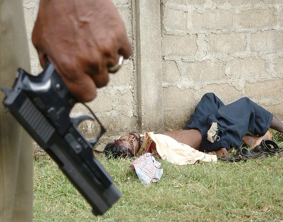 Police officer holds pistol near body of unidentified ethnic Tamil in Vavuniya