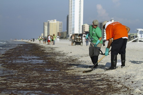 Workers shovel oil from the BP oil spill which made landfall in Gulf Shores, Alabama June 12, 2010