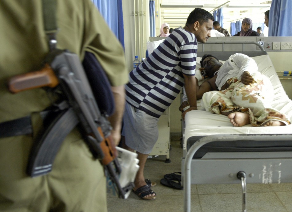 A Sri Lankan policeman stands guard beside the bed of K.P. Mohan, an ethnic Tamil Journalist, in the National Hospital in Colombo