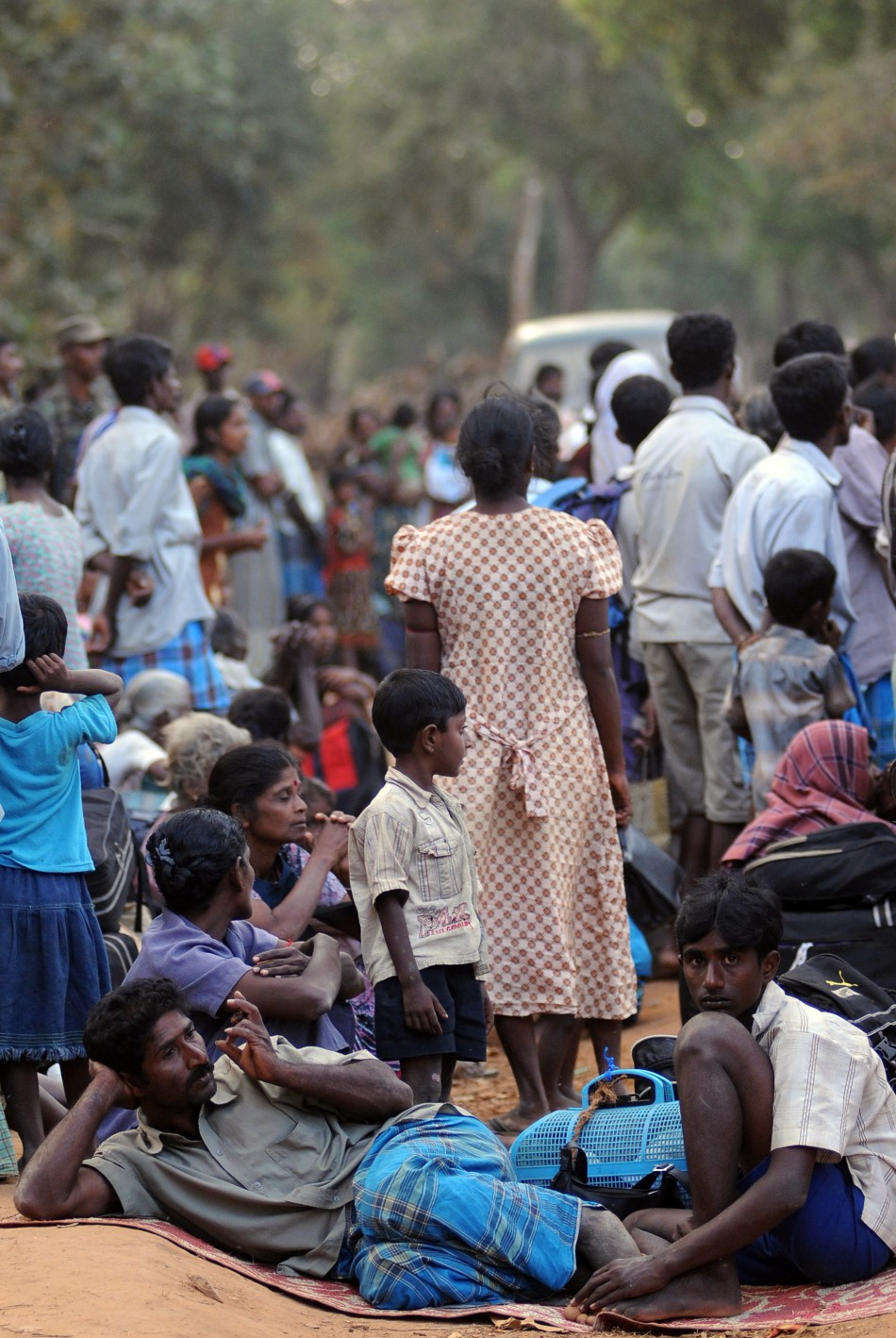 Tamils ethnic civilians wait to go to a camp for internally displaced people
