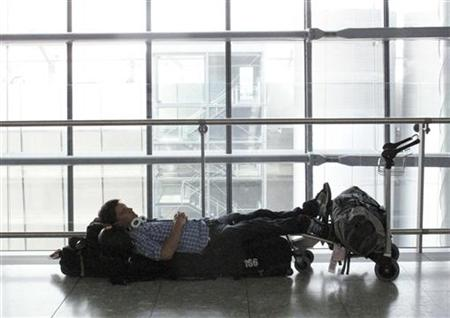 A passenger lays on luggage at Terminal 5 in Heathrow Airport