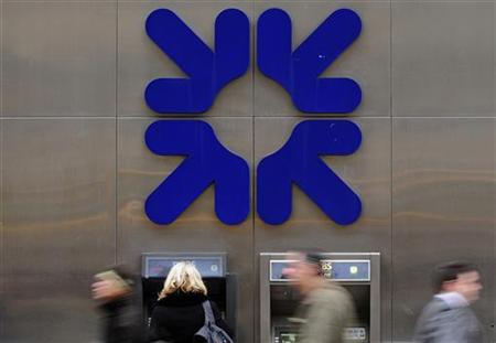 A woman uses an ATM at a Royal Bank of Scotland branch in the City of London