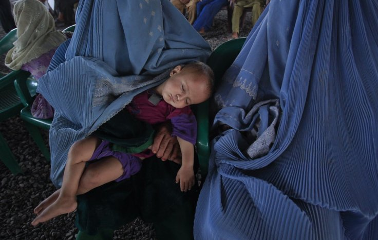 A child sleeps while Afghan refugees wait to be repatriated from a centre in Peshawar