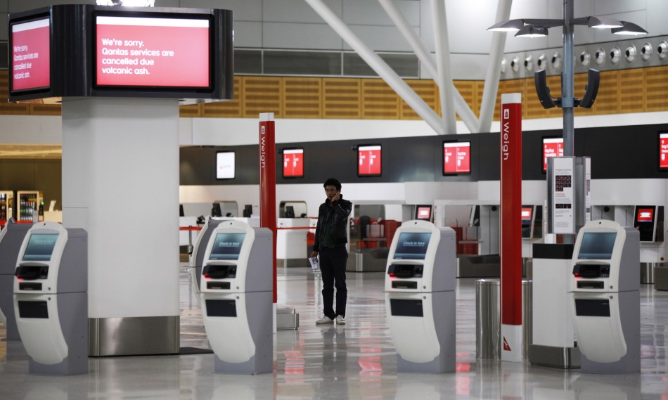A passenger uses his mobile phone at the almost deserted Qantas domestic terminal in Sydney's airport