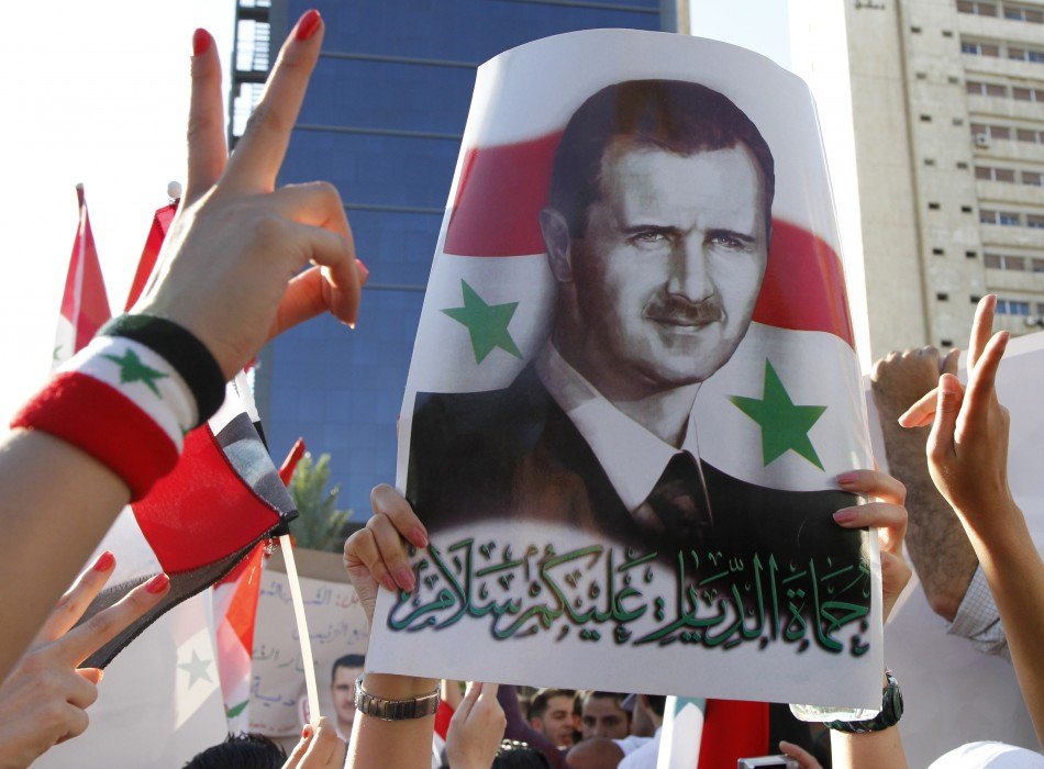 A pro-Syrian President Bashar al-Assad supporter, who rallied to a Facebook call to sit-in to support the army at Arnous square, carries his picture in Damascus