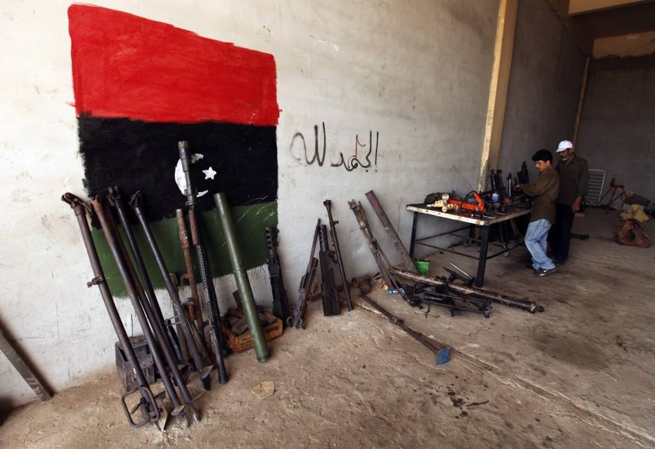 Rebel army officers fix weapons taken from forces loyal to Libyan leader Muammar Gaddafi at a workshop in Benghazi