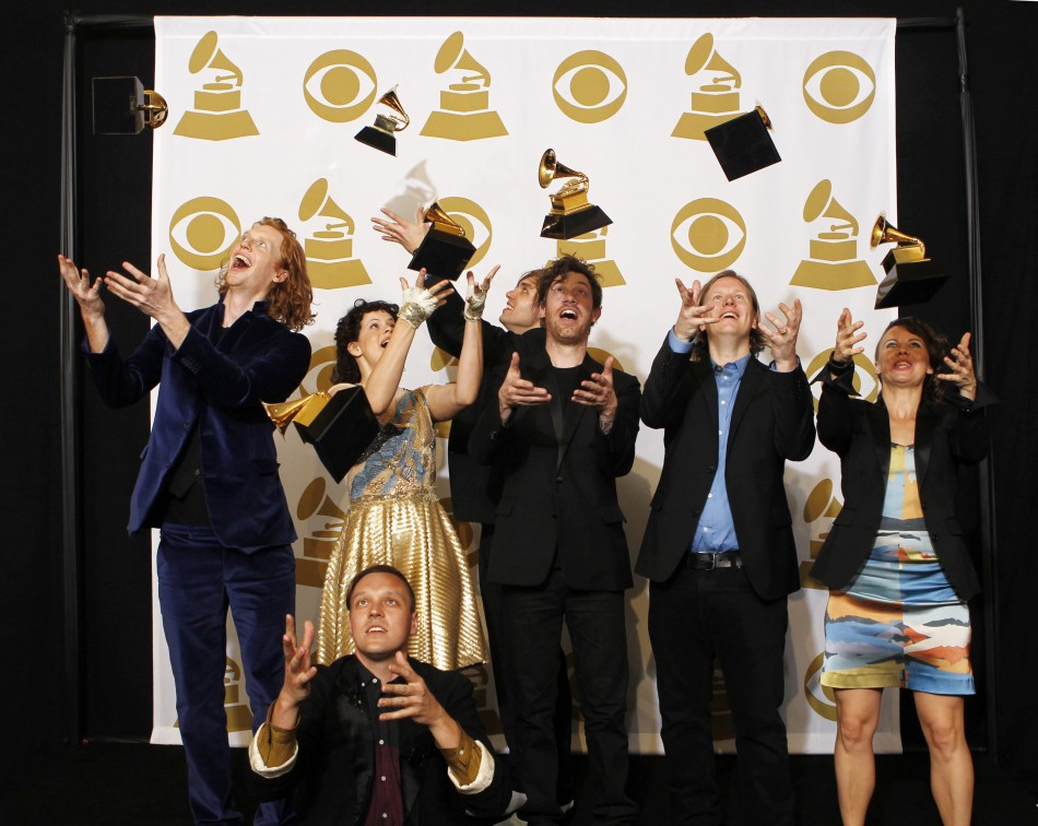 Rock group Arcade Fire throws their awards in the air at the 53rd annual Grammy Awards in Los Angeles