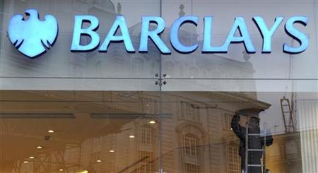A worker carries out maintenance in a branch of Barclays bank in London