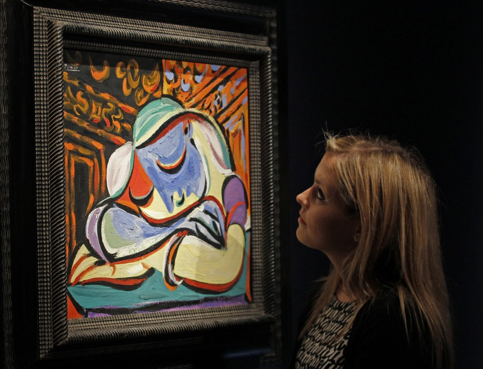 """A employee poses with Pablo Picasso's """"Jeune fille endormie"""" at Christie's auction house in London"""