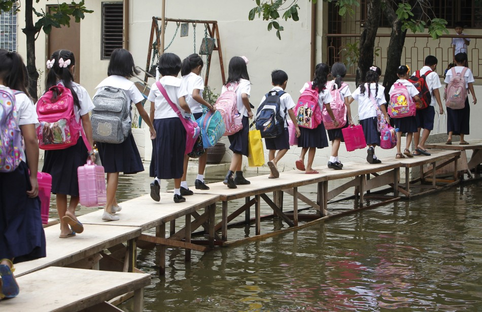 School children cross a flooded area brought by Typhoon Sepat in Valenzuela city, north of Manila