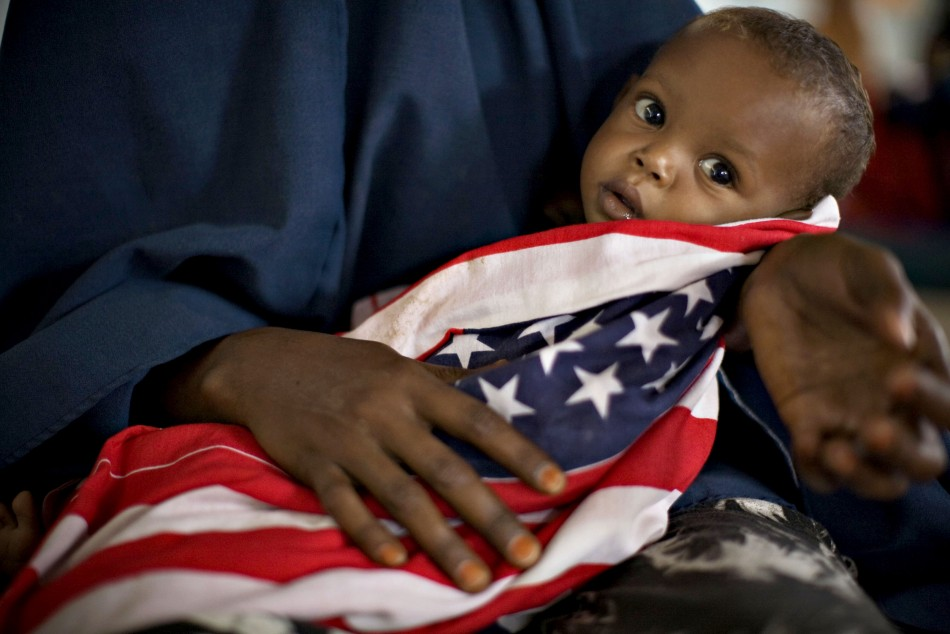 "A malnourished Somali child is wrapped in an American ""Stars and Stripes"" cloth at a therapeutic feeding center at Dagahaley camp"