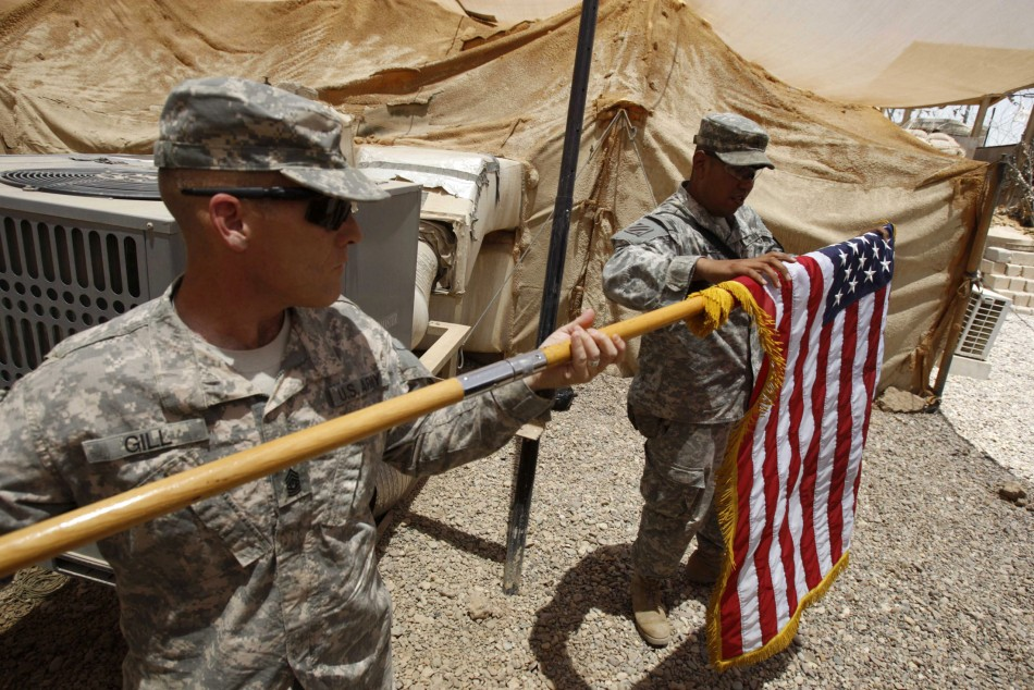 U.S. soldiers fold their national flag as they prepare to hand over their base to Iraqi forces
