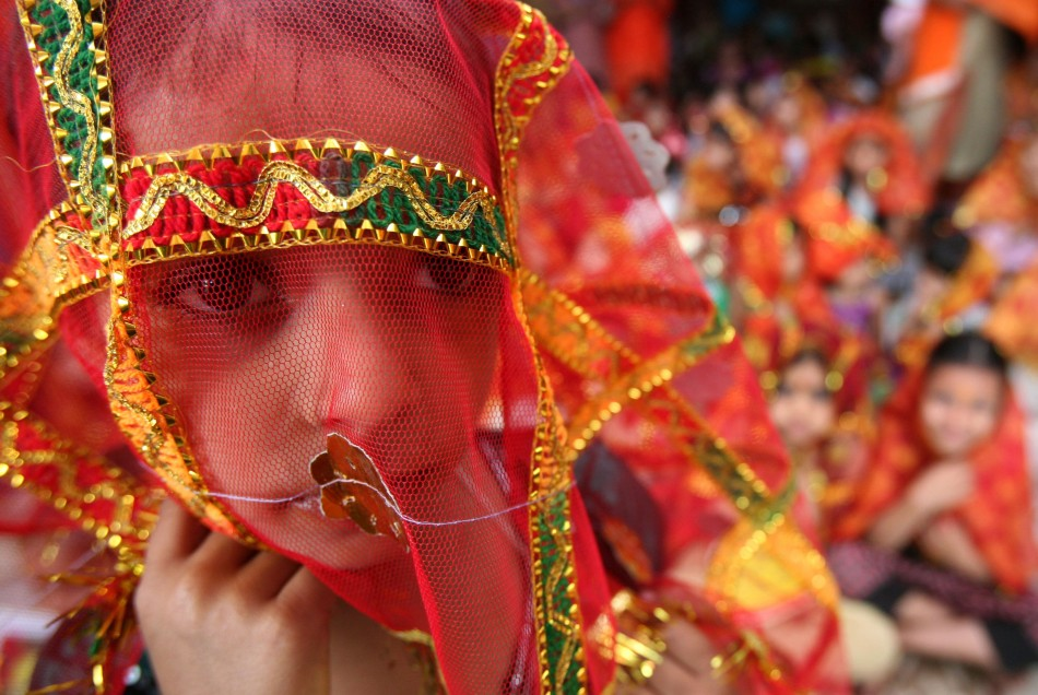 "A girl attends a prayer ceremony inside a temple during celebrations to mark the ""Navratri"" festival in Chandigarh"