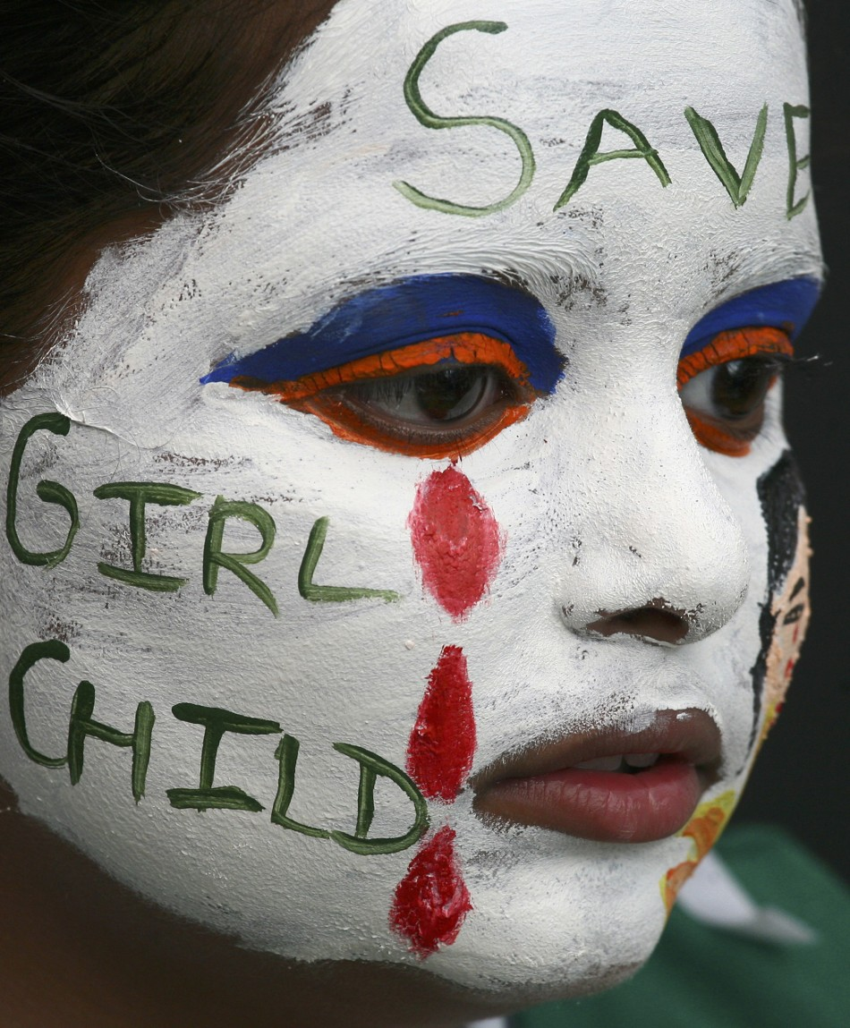 A girl with her face painted with an awareness message on female foeticide