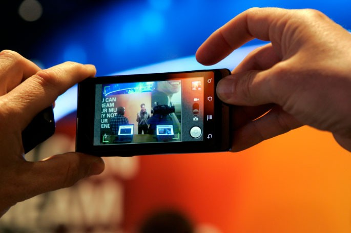 A man takes a photo with a Motorola Milestone smartphone, sister phone to the Motorola Droid, during the 2010 International Consumer Electronics Show (CES) in Las Vegas, Nevada January 8, 2010