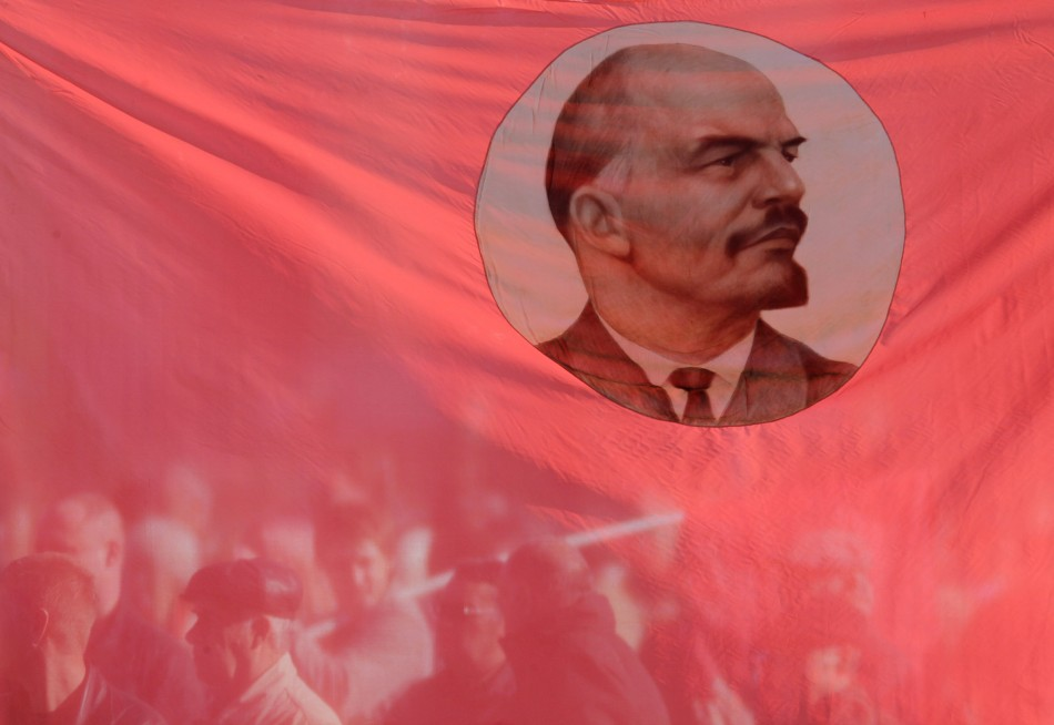 Russian communist supporters are seen through a flag, displaying an image of Soviet state founder Vladimir Lenin, during a rally to mark the anniversary of the 1917 Bolshevik revolution in Stavropol