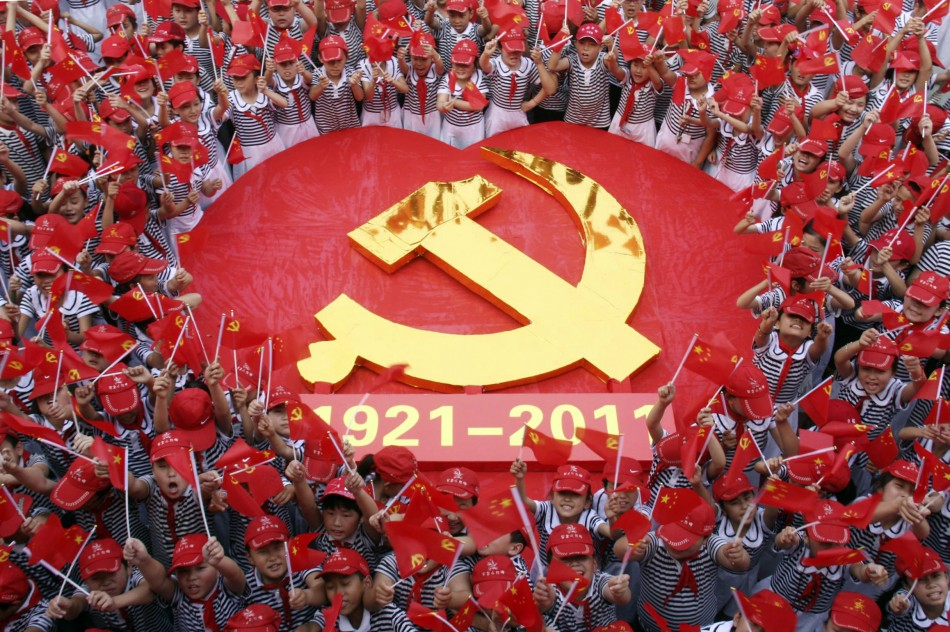 Students wave flags of the CPC as they pose for a photo with an emblem of the CPC at a primary school in Zaozhuang, Shandong province