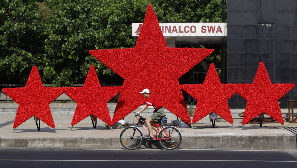 A man cycles past a decoration put up to celebrate the upcoming 90th anniversary of the founding of the CPC in Chongqing municipality