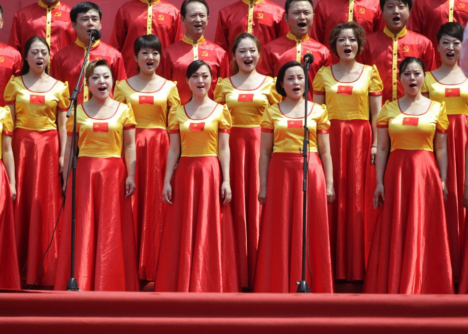 Students wave flags of CPC during opening ceremony of a revolutionary song singing concert in Chongqing municipality