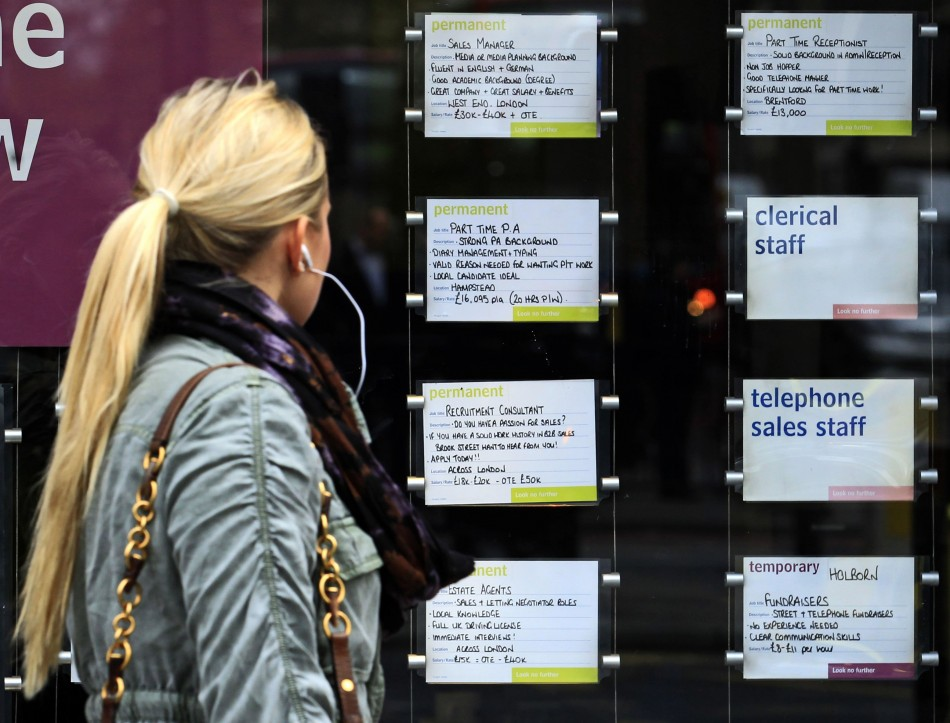 A woman passes notices for jobs in the window of a recruitment agency.