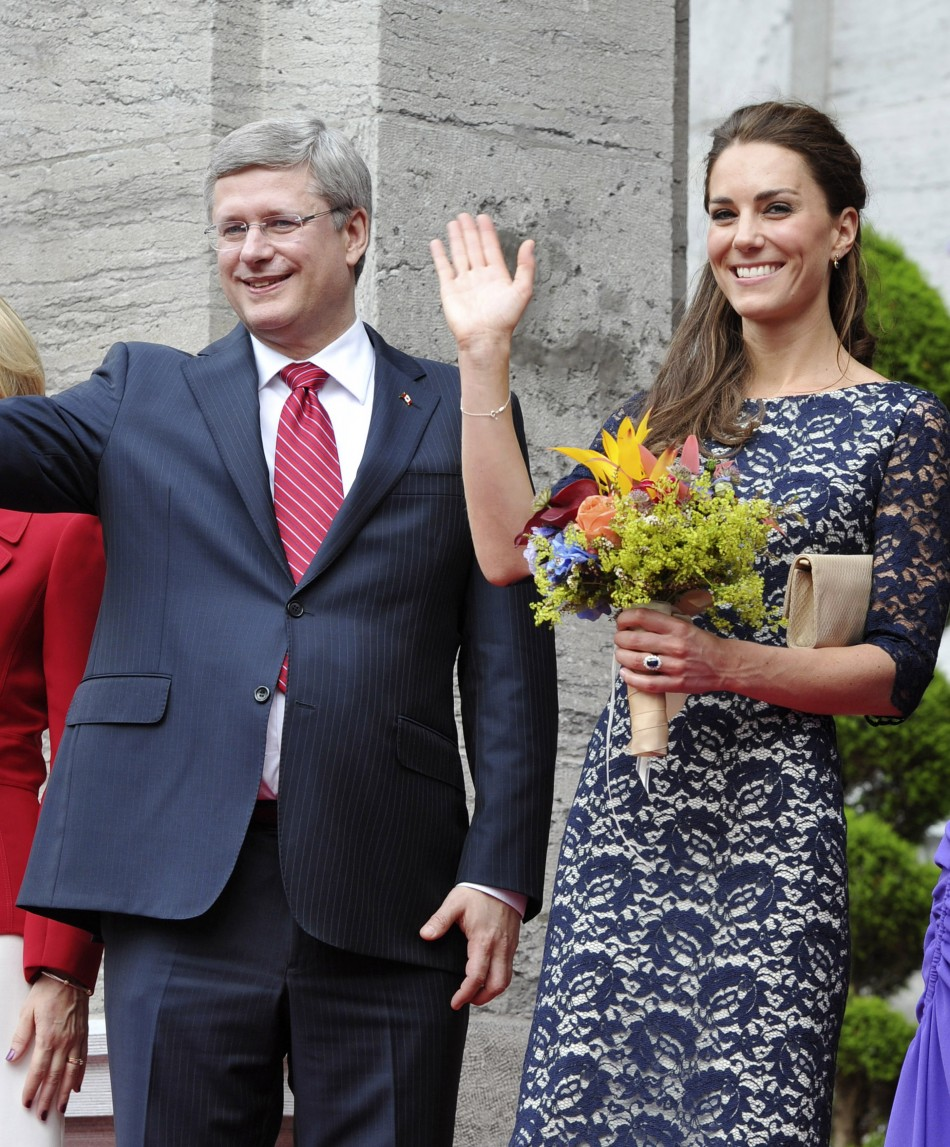 Britains Catherine, Duchess of Cambridge, waves as she stands with Canadas Prime Minister Stephen Harper in Ottawa