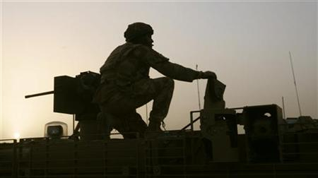 A British soldier is seen holding on to the turret gun of a manoeuvring armoured vehicle in Lashkar Gah