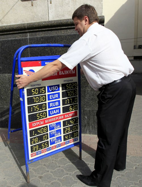 An employee places a board displaying currency rates outside a bank in the capital Minsk