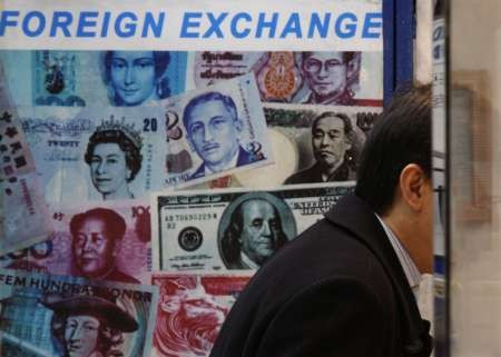 A customer is served at a counter inside a foreign exchange store displaying a poster of various banknotes including the Chinese yuan or renminbi (RMB) in Hong Kong November 20, 2009.