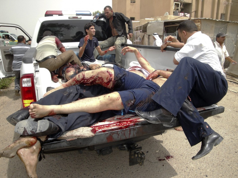 Bodies are loaded onto a police vehicle near the site of bombings in the town of Taji