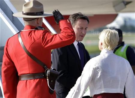 A Royal Canadian Mounted Police officer salutes as Britain's Prime Minister Cameron arrives at Pearson International Airport for the G8 and G20 summits in Toronto