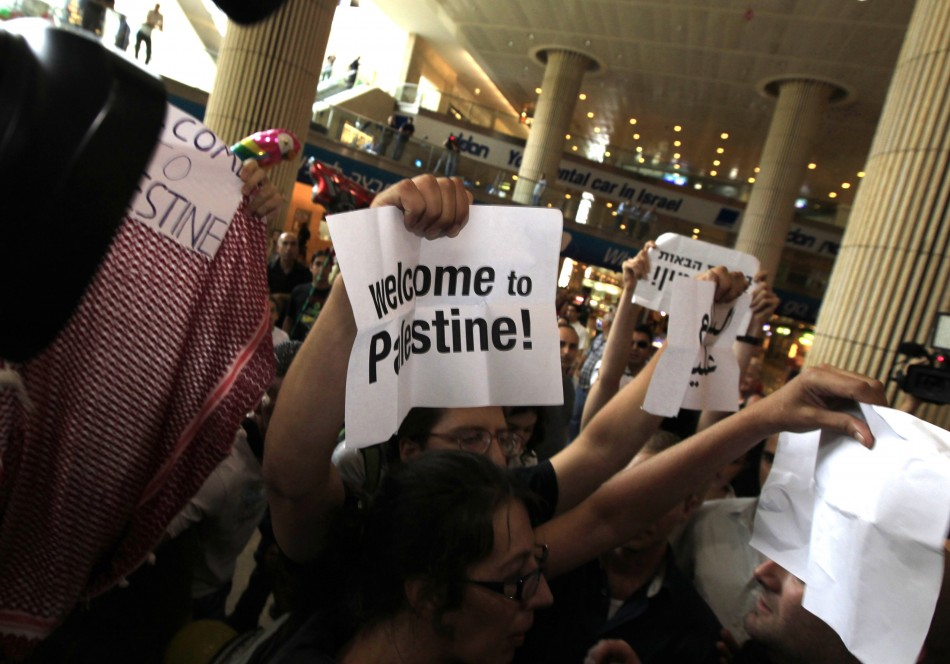 Pro-Palestinian Israeli activists hold signs during a protest at Ben Gurion International Airport near Tel Aviv