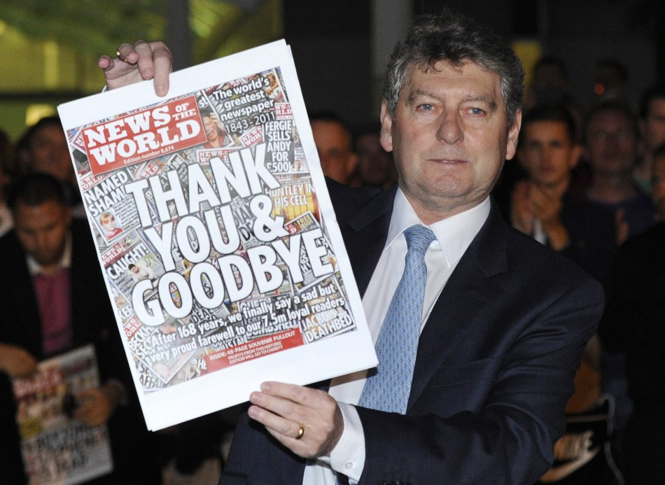 Colin Myler, editor of the News of The World, holds up a copy of the last edition of the newspaper outside the newspaper's office in Wapping