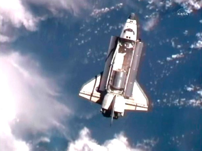 The space shuttle Atlantis is seen with earth in the background as it draws near the International Space Station for docking