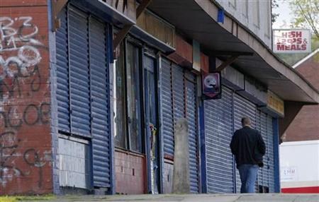 A man walks past a parade of closed shops in Liverpool.
