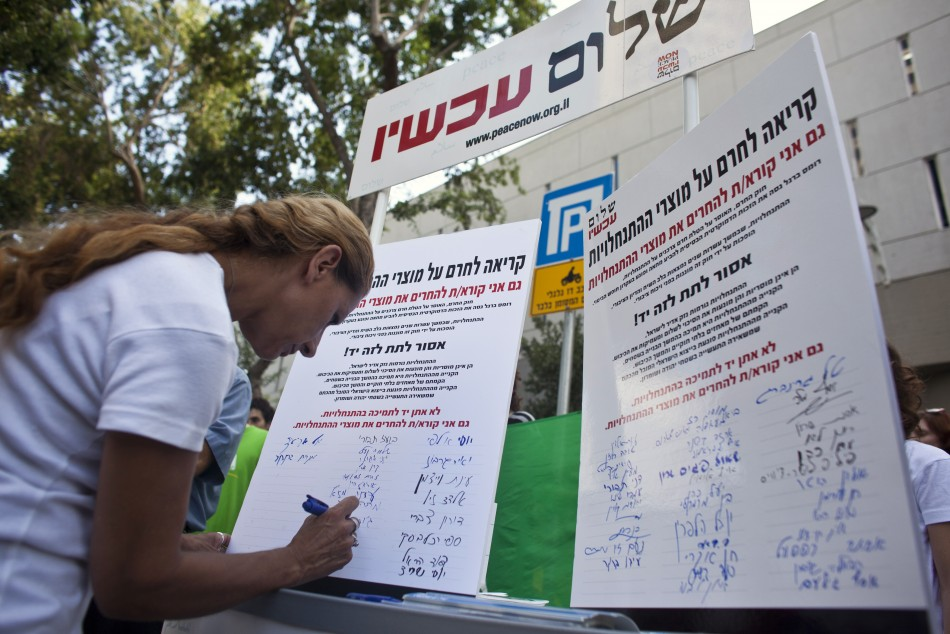 A woman signs a Peace Now petition in Tel Aviv, calling for a boycott of settlement products