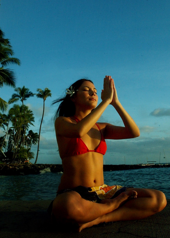 WOMAN MEDITATES ON HAWAI BEACH.