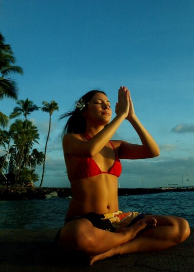 WOMAN MEDITATES ON HAWAI BEACH.