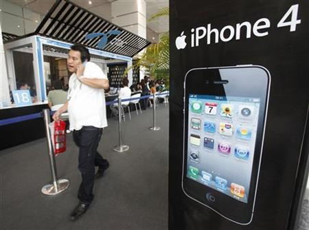 A man walks past an advertisement for an iPhone 4 displayed at a shop in Bangkok