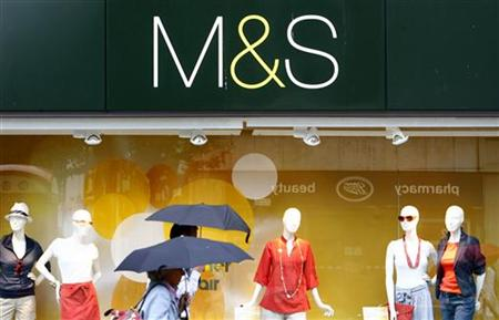 Shoppers walk past a Marks and Spencer store in central London
