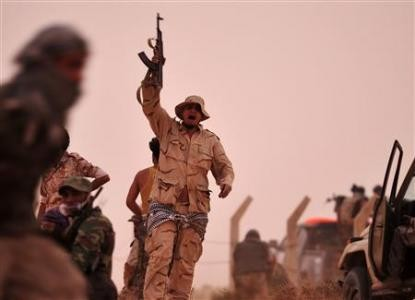 A rebel fighter holds a weapon during a shootout with forces loyal to Libya's leader Muammar Gaddafi on the outskirts of Al-Briqa, west of Ajdabiyah