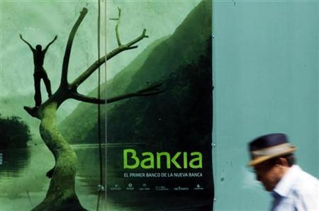 A man walks past a poster of savings bank Bankia in Madrid