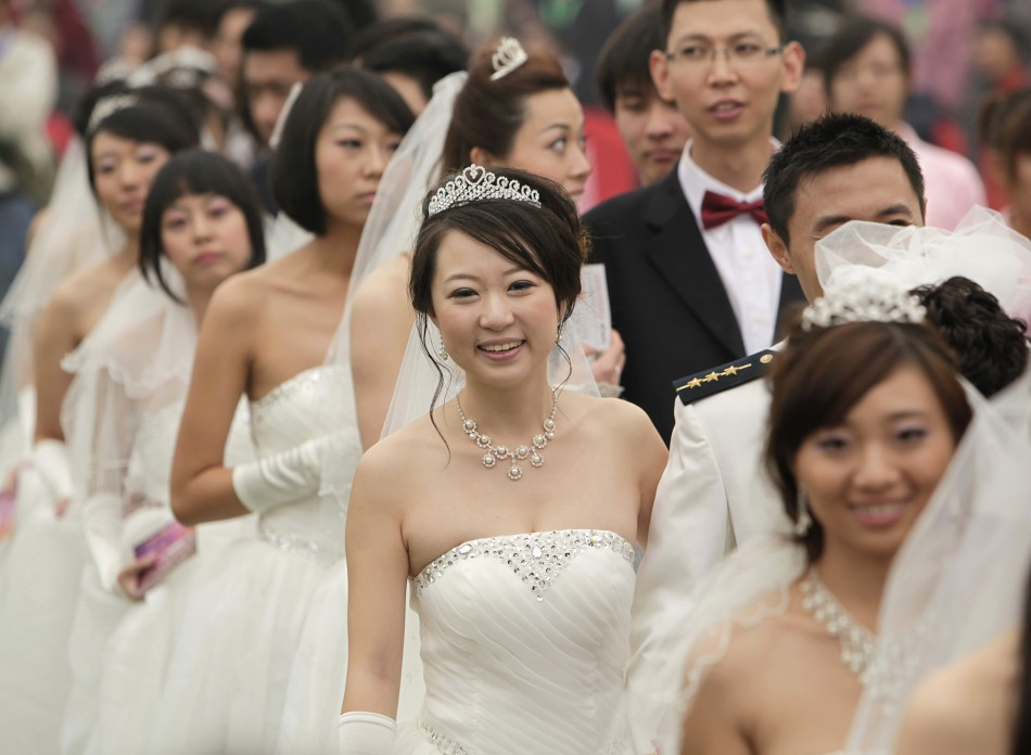 Couples take part in a mass wedding ceremony at the Olympic Park in Beijing October 10, 2010. Sixty couples took part in a mass wedding ceremony which started at 10:10 in the morning on the tenth day of the tenth month in the tenth year of the 21st centur