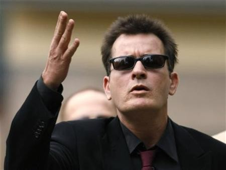 Charlie Sheen gestures towards fans as he arrives for a sentencing hearing at the Pitkin County Courthouse in Aspen, Colorado